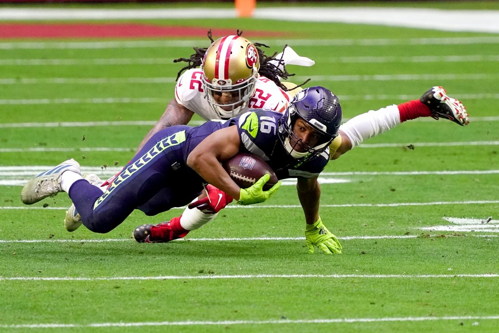 Seattle Seahawks cornerback Quinton Dunbar (22) tackles Seattle Seahawks wide receiver Tyler Lockett (16) during the first half of an NFL football gam...