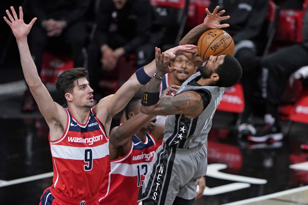 Washington Wizards forward Deni Avdija, left, tips the ball from Brooklyn Nets guard Kyrie Irving, right, during the first quarter of an NBA basketbal...