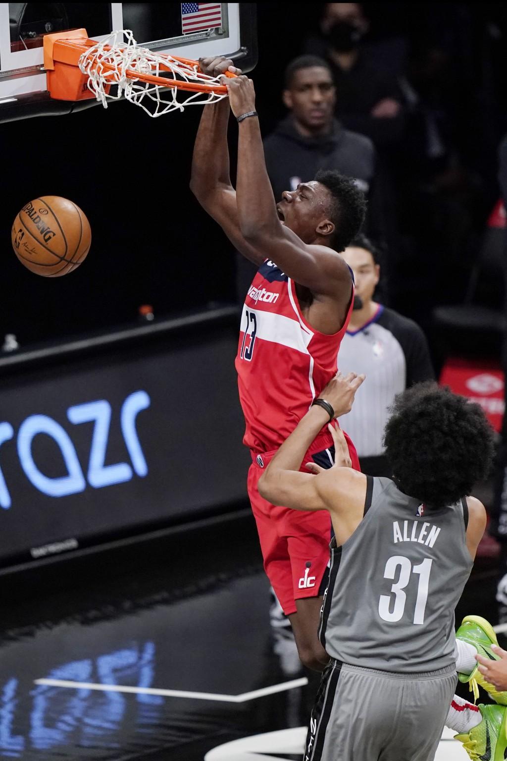 Washington Wizards center Thomas Bryant (13) dunks over Brooklyn Nets center Jarrett Allen (31) during the third quarter of an NBA basketball game, Su...