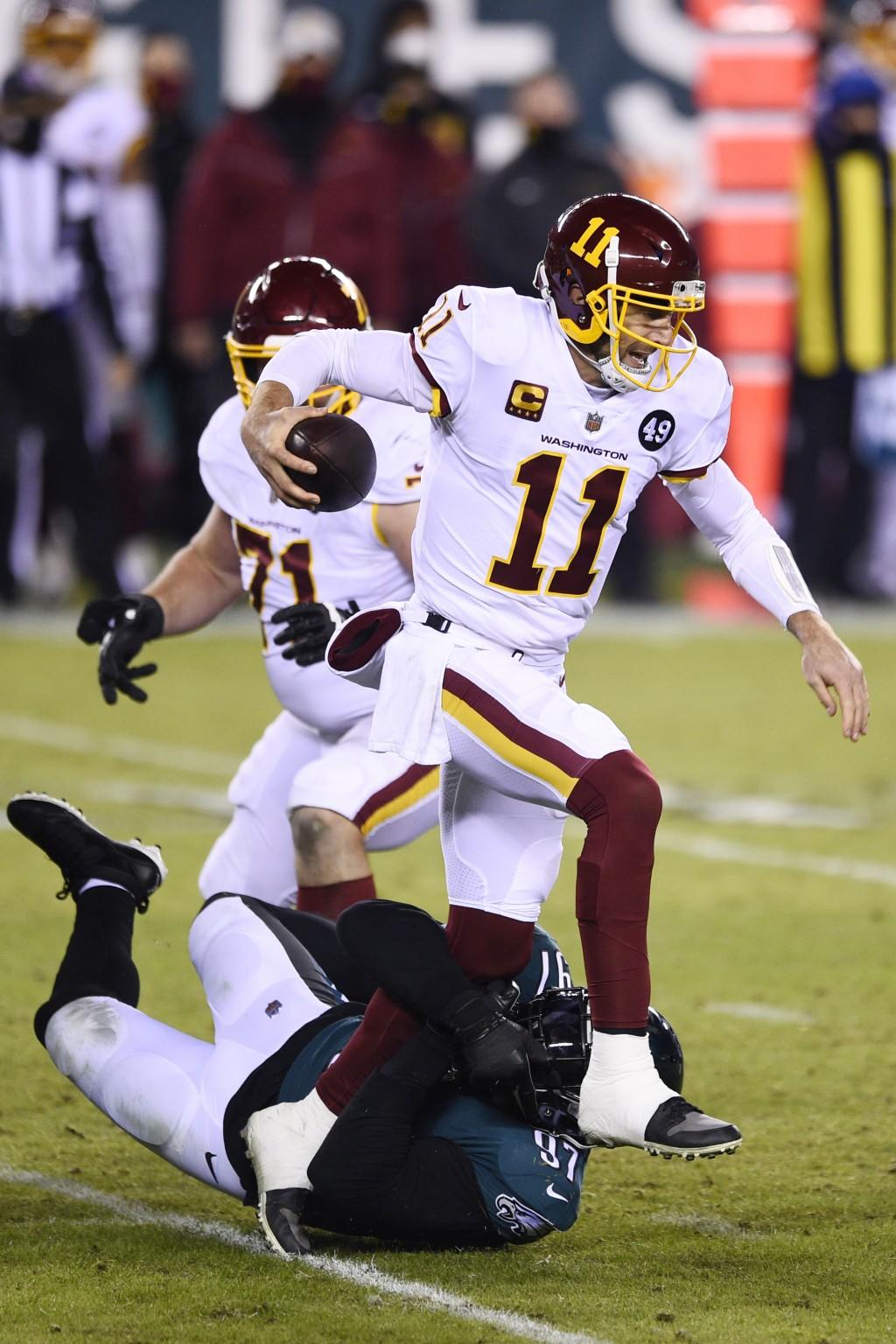 Washington Football Team's Alex Smith (11) is tackled by Philadelphia Eagles' Malik Jackson (97) during the second half of an NFL football game, Sunda...