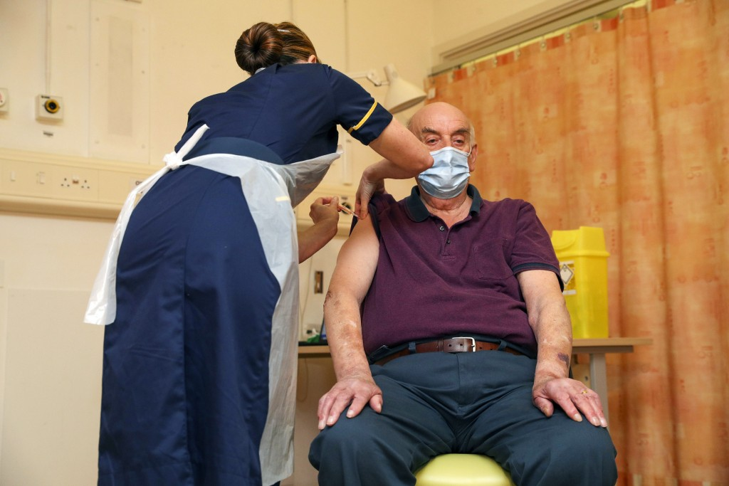 82-year-old Brian Pinker receives the Oxford University/AstraZeneca COVID-19 vaccine from nurse Sam Foster at the Churchill Hospital in Oxford, Englan...
