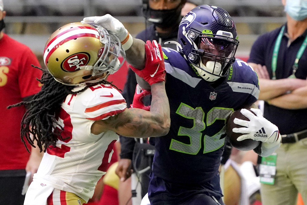 Seattle Seahawks running back Chris Carson (32) stiff arms San Francisco 49ers cornerback Jason Verrett (22) during the first half of an NFL football ...
