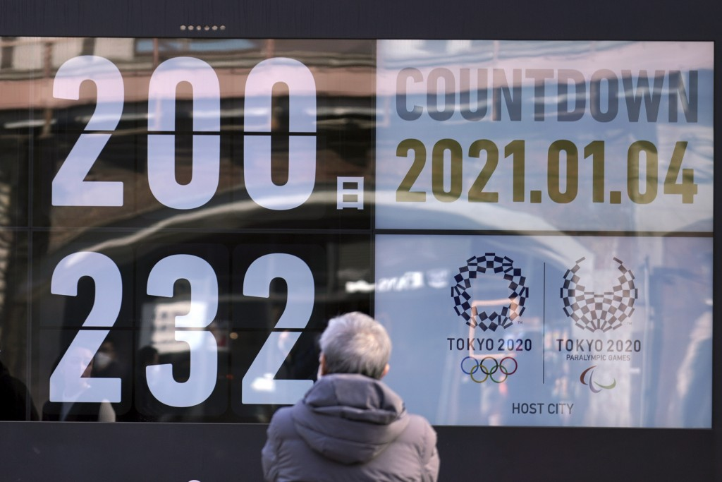 A man looks at a countdown calendar showing 200 day to start Tokyo 2020 Olympics Monday, Jan. 4, 2021, in Tokyo. The countdown clock for the postponed...