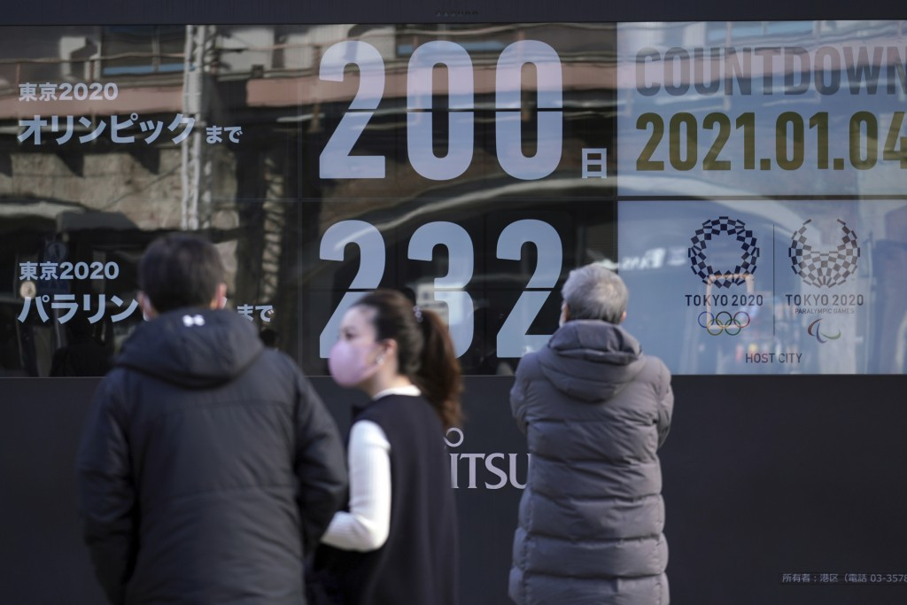People wearing masks against the spread of the coronavirus walk in front of a countdown calendar showing 200 day to start Tokyo 2020 Olympics Monday, ...