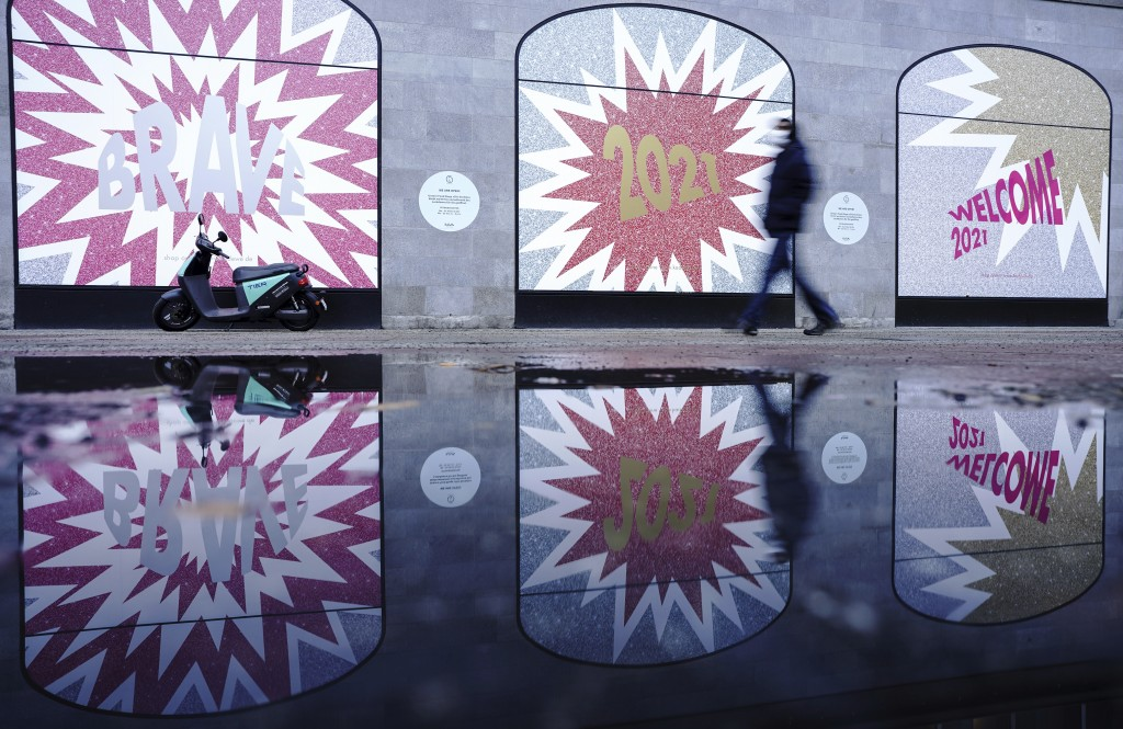 A pedestrian walks past a window of the largely closed KaDeWe department store in the morning with the 2021 logo pasted on it in Berlin, Germany, Tues...