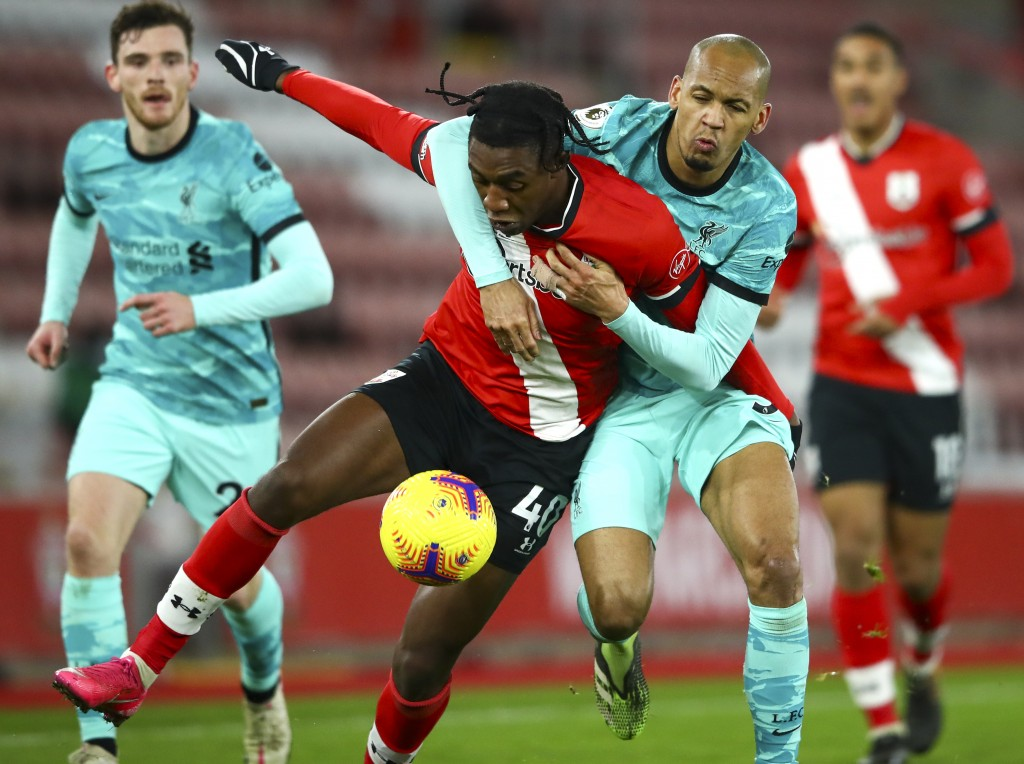 Southampton's San Nlundulu, left, and Liverpool's Fabinho battle for the ball during the English Premier League soccer match between Southampton and L...