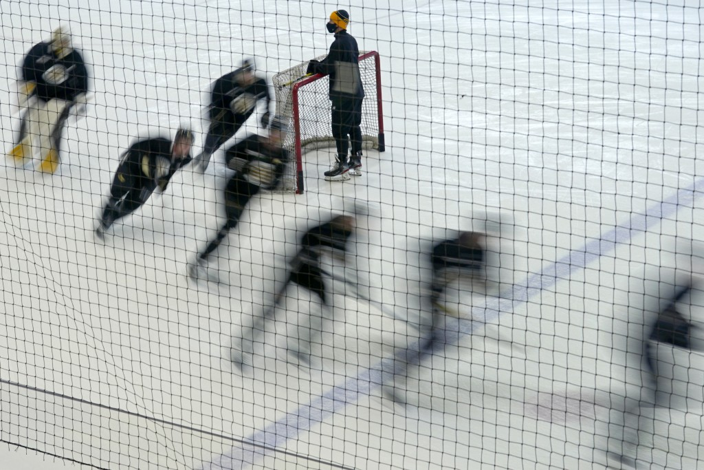 Boston Bruins players skate around a goal during a speed drill at the team's NHL hockey training camp, Monday, Jan. 4, 2021, in Boston. (AP Photo/Elis...