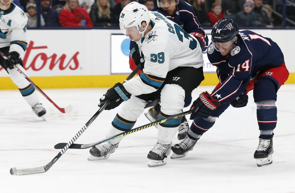 FILE - In this Jan. 4, 2020, file photo, San Jose Sharks' Logan Couture, left, skates the puck upice as Columbus Blue Jackets' Gustav Nyquist, of Swed...