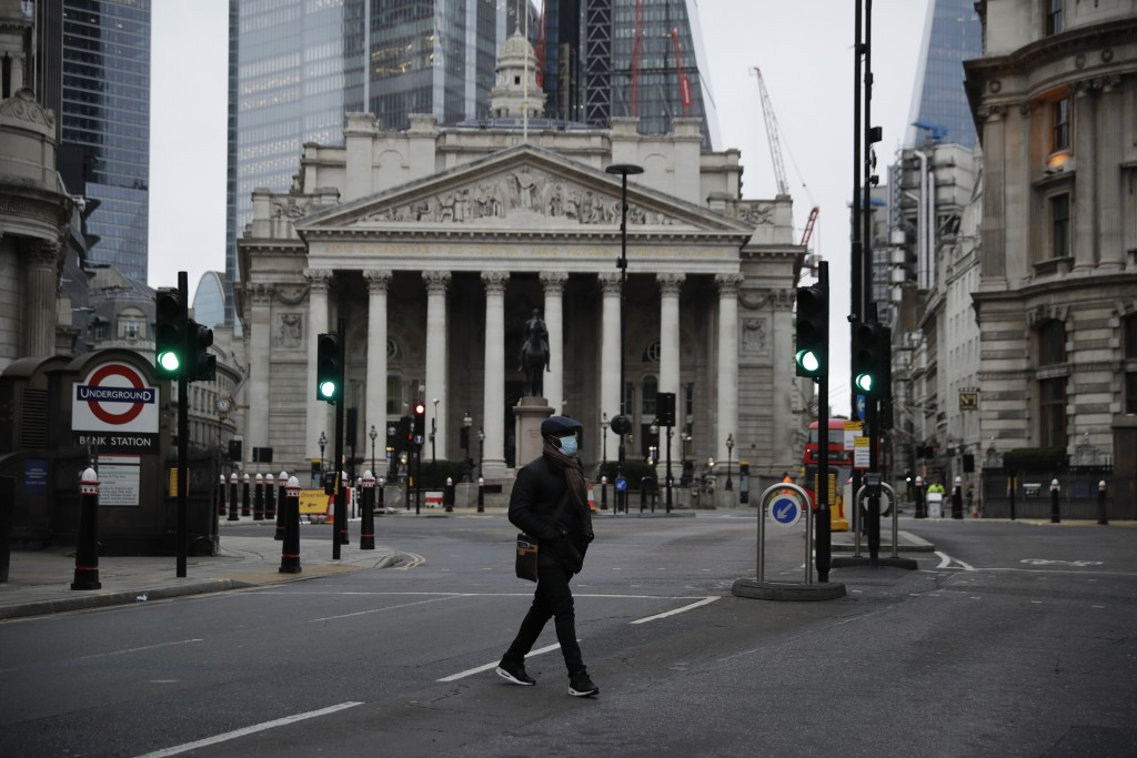 A man crosses the street backdropped by the Royal Exchange in the City of London financial district in London, Jan. 5, 2021, on the first morning of E...