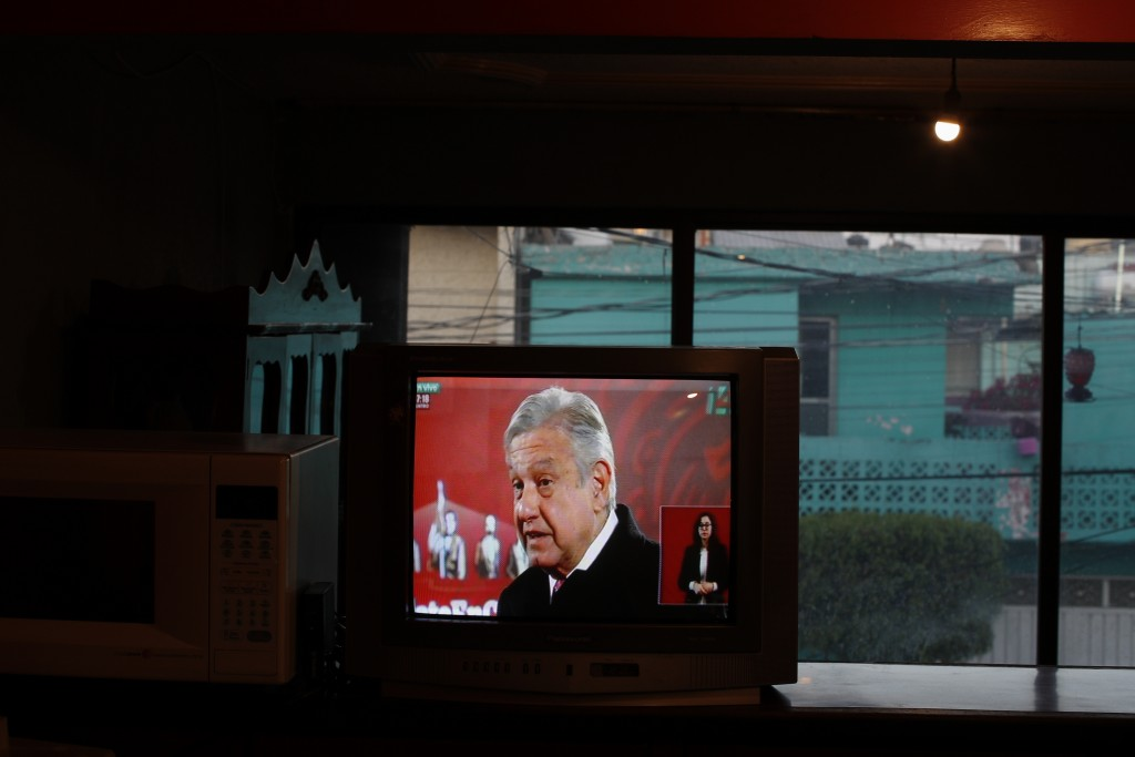 Mexico's President Andres Manuel Lopez Obrador is seen on a TV screen as Rafael Silva watches the live broadcast of the president's daily, morning pre...