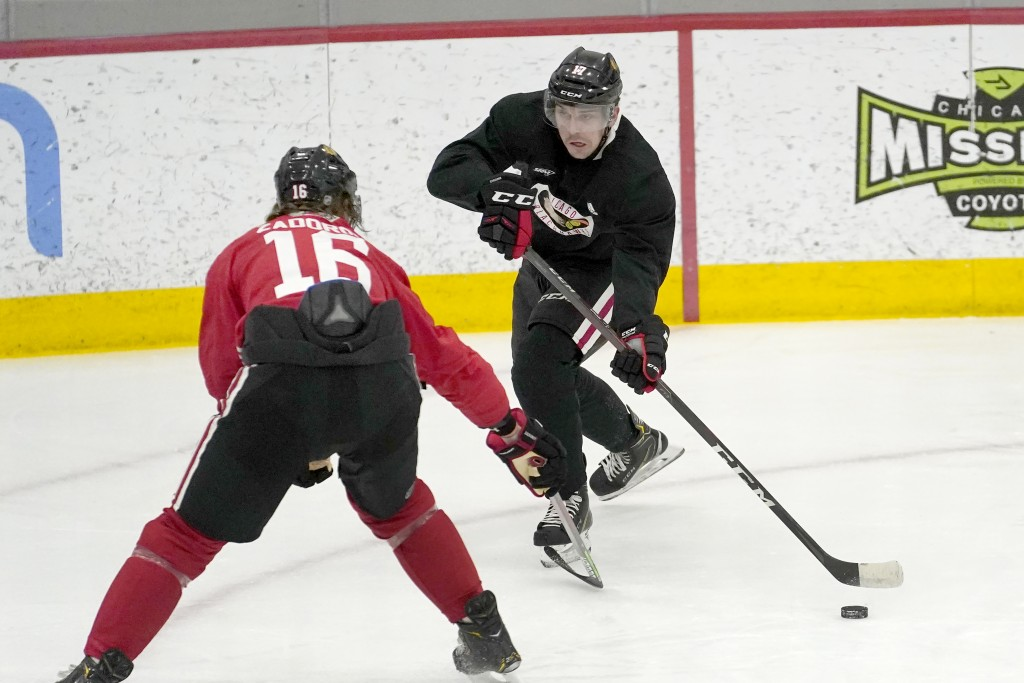 Chicago Blackhawks' Dylan Strome, right, looks to pass past Nikita Zadorov during an NHL hockey training camp practice Monday, Jan. 4, 2021, in Chicag...