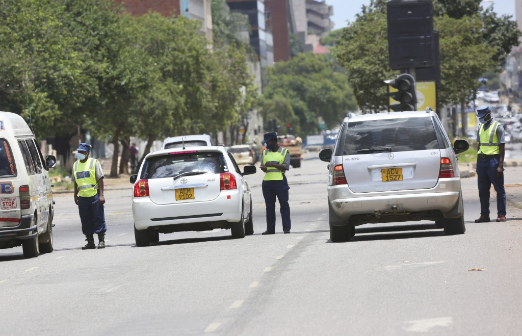 Police stop motorists on the streets of Harare, Tuesday, Jan, 5, 2021, as Zimbabwe has began a 30-day lockdown in a bid to rein in the spike in COVID ...