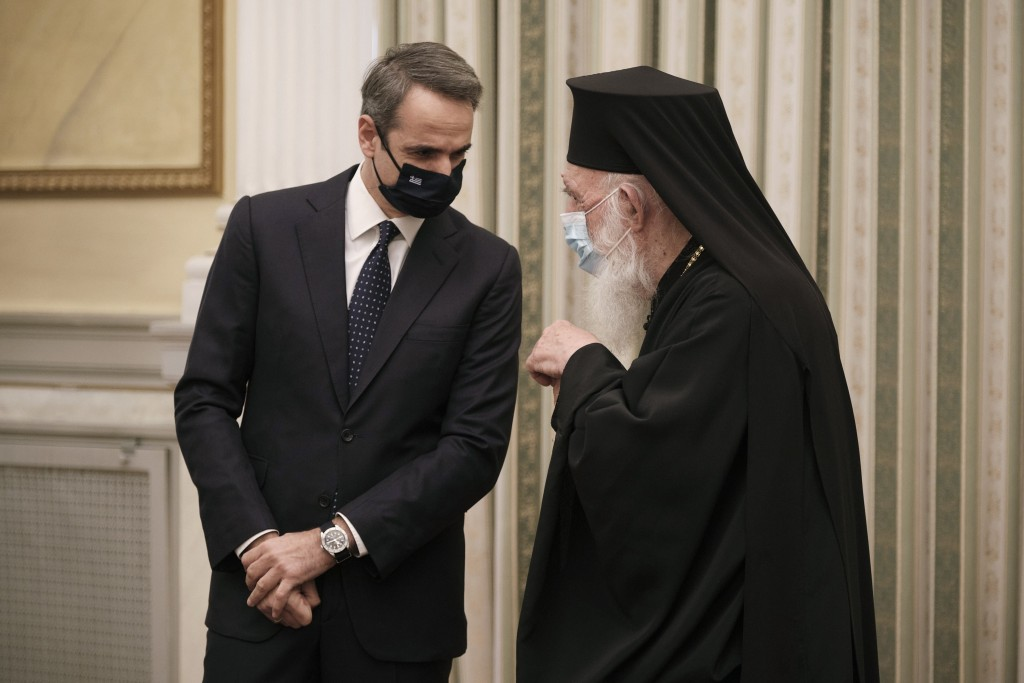 In this photo provided by the Greek Prime Minister's Office, Greece's Prime Minister Kyriakos Mitsotakis, left, talks with Archbishop of Athens and Al...