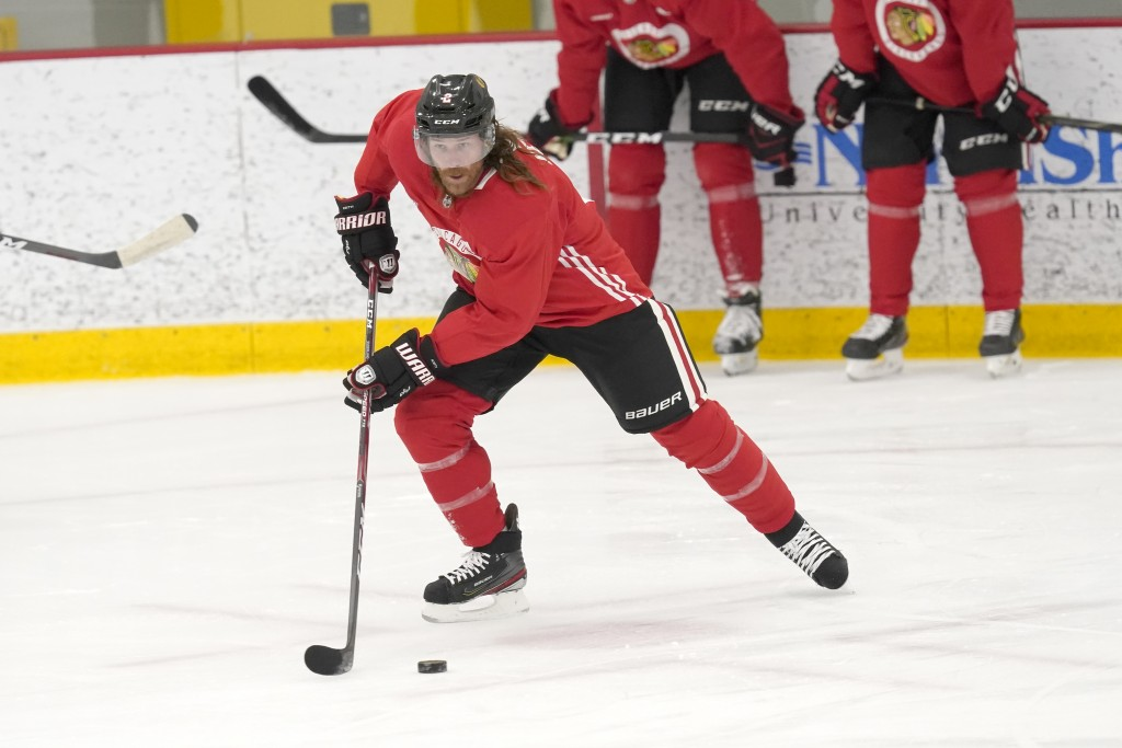 Chicago Blackhawks' Duncan Keith handles the puck during an NHL hockey training camp practice Monday, Jan. 4, 2021, in Chicago. (AP Photo/Charles Rex ...