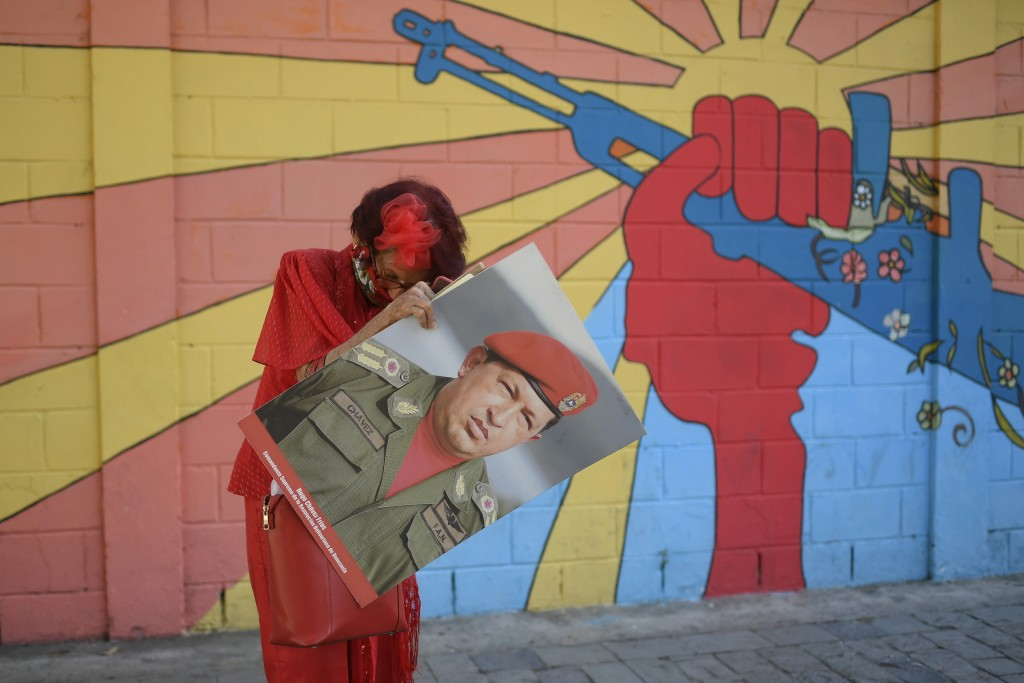 """A government supporter known as """"Caperucita,"""" or Little Red Riding Hood, holds a photo of late Venezuelan President Hugo Chavez as she looks for somet..."""