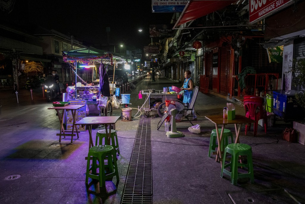A lone street vender waits for customers at Khao San road, a once popular hangout with bars and entertainment for locals and tourists in Bangkok, Thai...