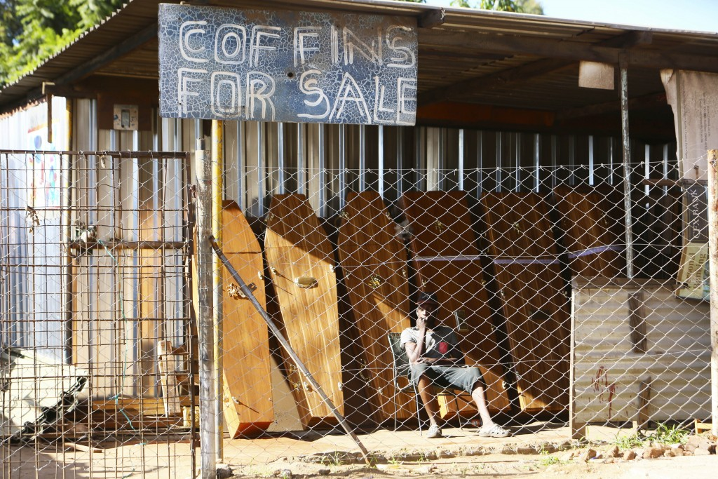 A worker at a coffin making company waits for clients inside the company premises in Harare, Tuesday, Jan. 5, 2021, as Zimbabwe began a 30-day lockdow...