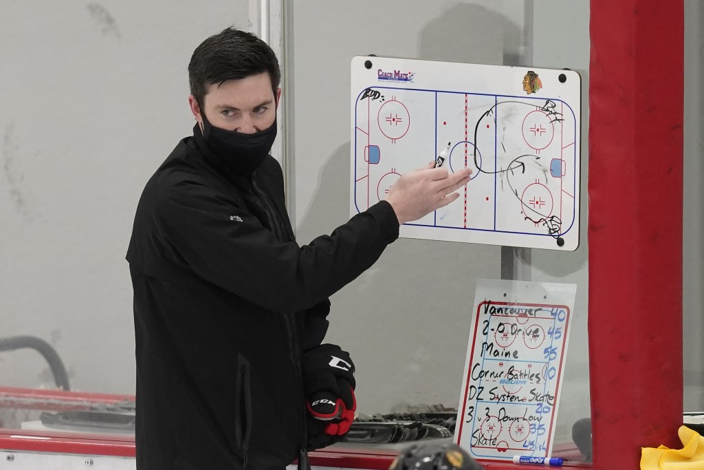 Chicago Blackhawks head coach Jeremy Colliton sets up a drill during an NHL hockey training camp practice Monday, Jan. 4, 2021, in Chicago. (AP Photo/...
