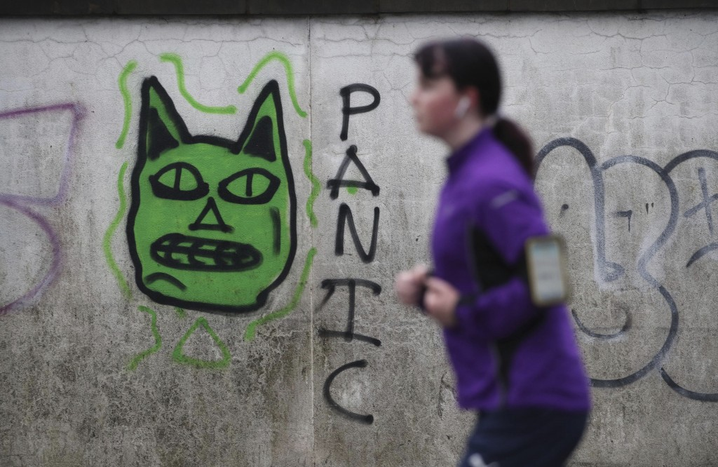 A woman runs past some graffiti in Edinburgh, the morning after stricter COVID-19 lockdown measures came into force for mainland Scotland, Tuesday Jan...
