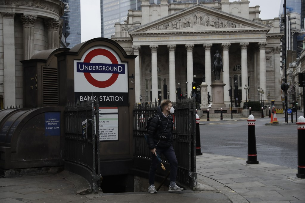 A man walks out of Bank underground train station backdropped by the Royal Exchange in the City of London financial district in London, Jan. 5, 2021, ...