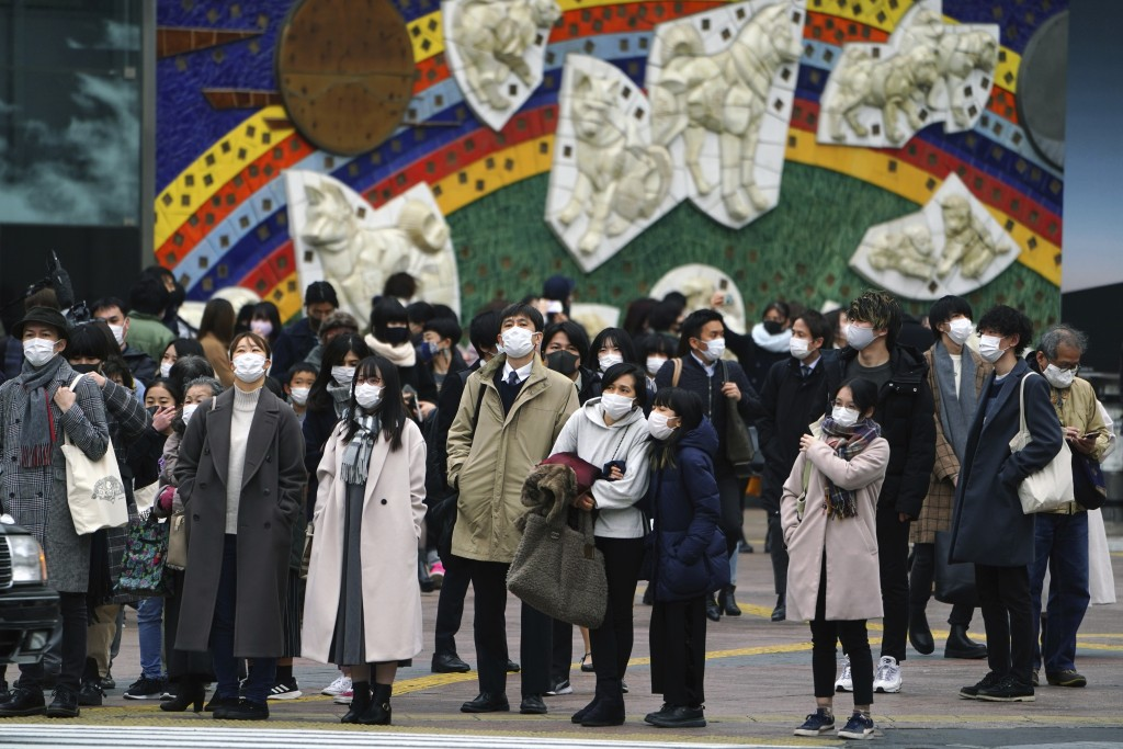 People wearing protective masks to help curb the spread of the coronavirus wait for traffic light to walk along pedestrian crossings in the Shibuya ar...