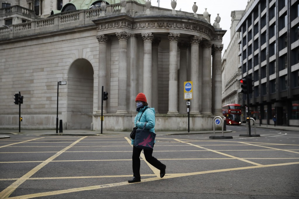 A woman walks past part of the Bank of England in the City of London financial district in London, Jan. 5, 2021, on the first morning of England enter...