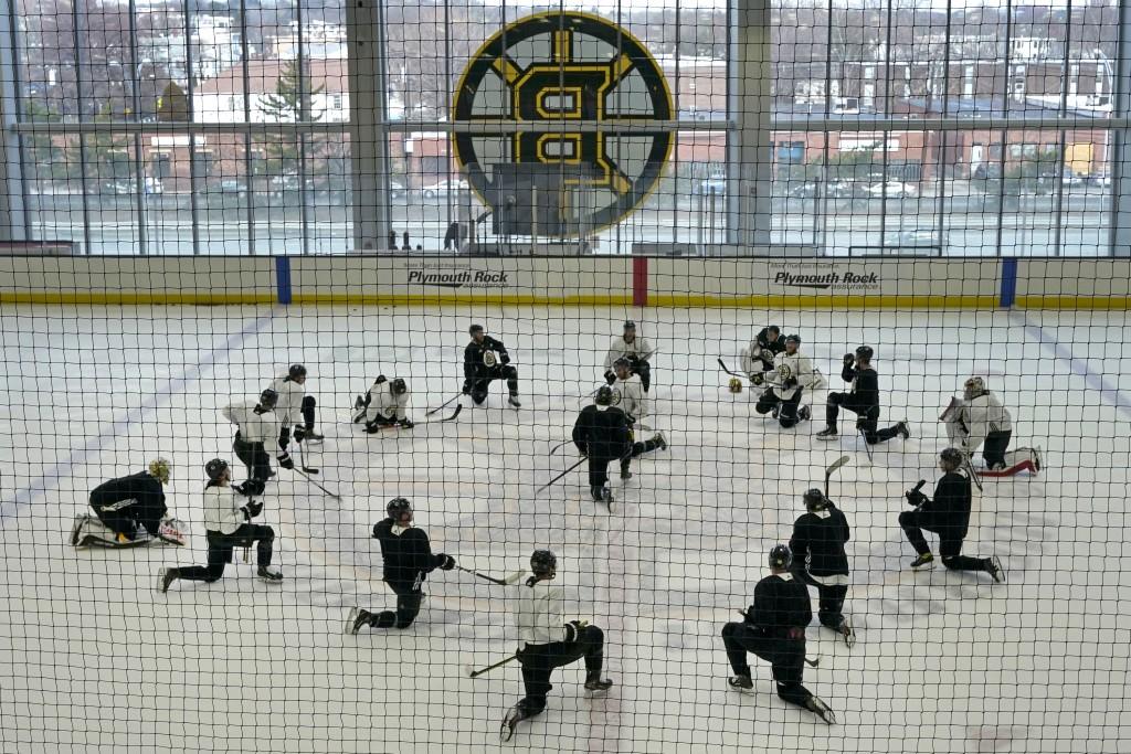 Boston Bruins players stretch at the team's NHL hockey training camp, Monday, Jan. 4, 2021, in Boston. (AP Photo/Elise Amendola)