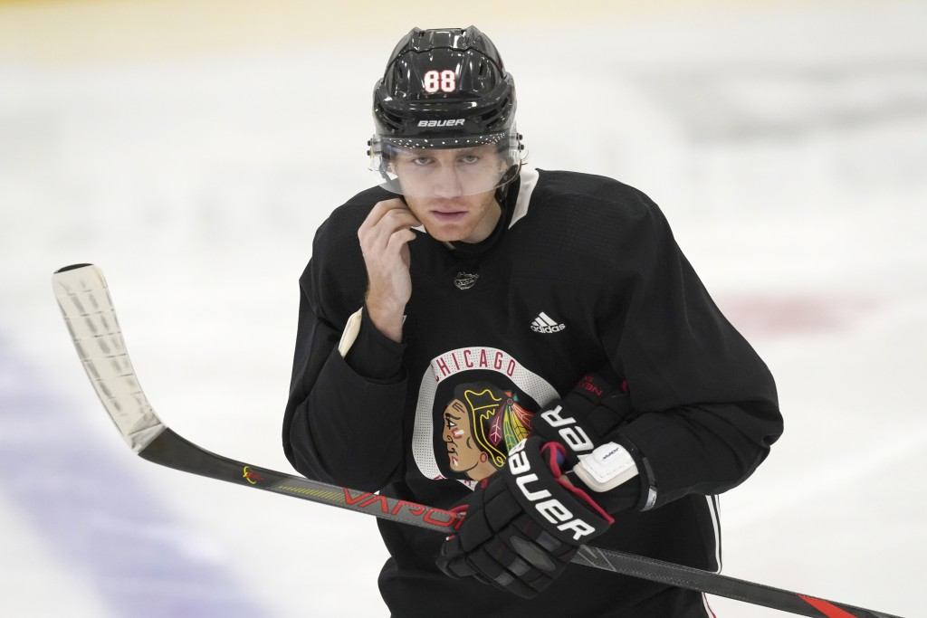 Chicago Blackhawks' Patrick Kane snaps on his helmet as he participates in an NHL hockey training camp practice Monday, Jan. 4, 2021, in Chicago. (AP ...