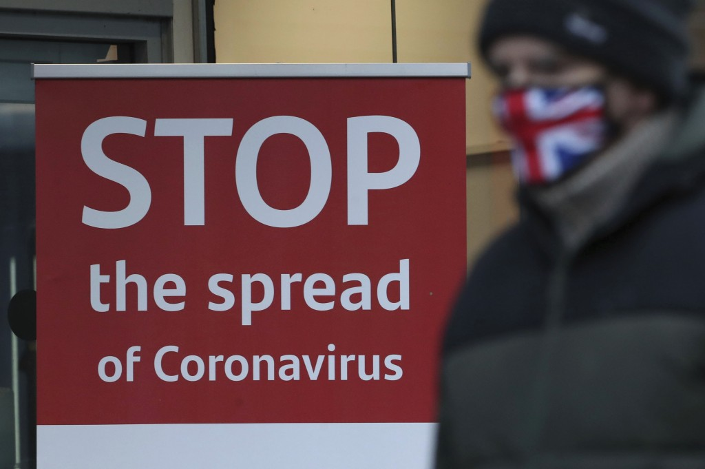 A man wearing a British union flag face mask walks past a coronavirus advice sign outside a bank in Glasgow the morning after stricter lockdown measur...