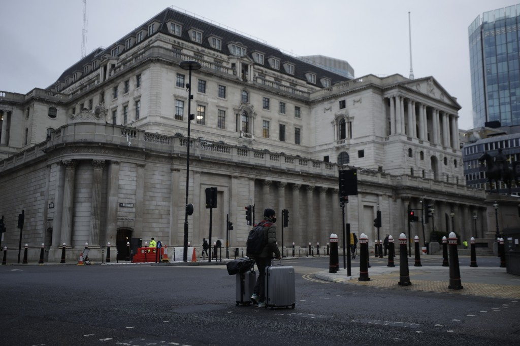 A man walks with luggage past the Bank of England in the City of London financial district in London, Jan. 5, 2021, on the first morning of England en...