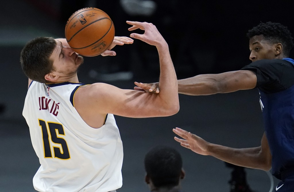 Denver Nuggets center Nikola Jokic, left, is hit by the ball after being fouled by Minnesota Timberwolves guard Jarrett Culver during the second half ...