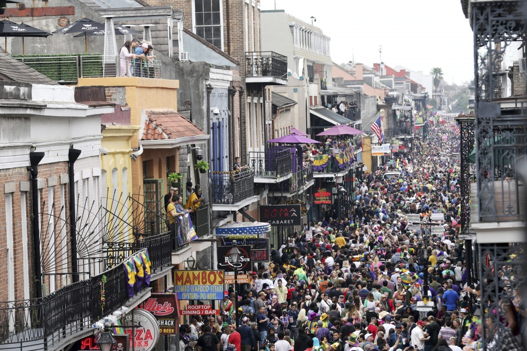 FILE - In this Tuesday, Feb. 25, 2020, file photo, Bourbon Street is a sea of humanity on Mardi Gras day in New Orleans. A subdued Carnival season beg...