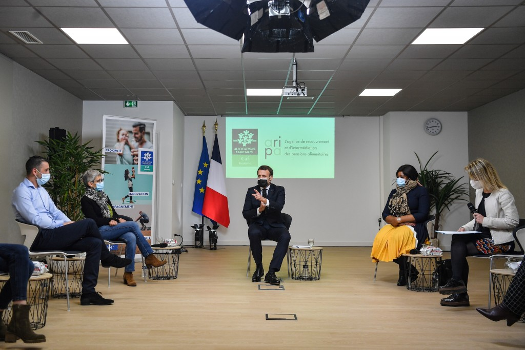 French President Emmanuel Macron, center, attends a meeting during a visit at the headquarters of the local CAF (French family allowance public servic...