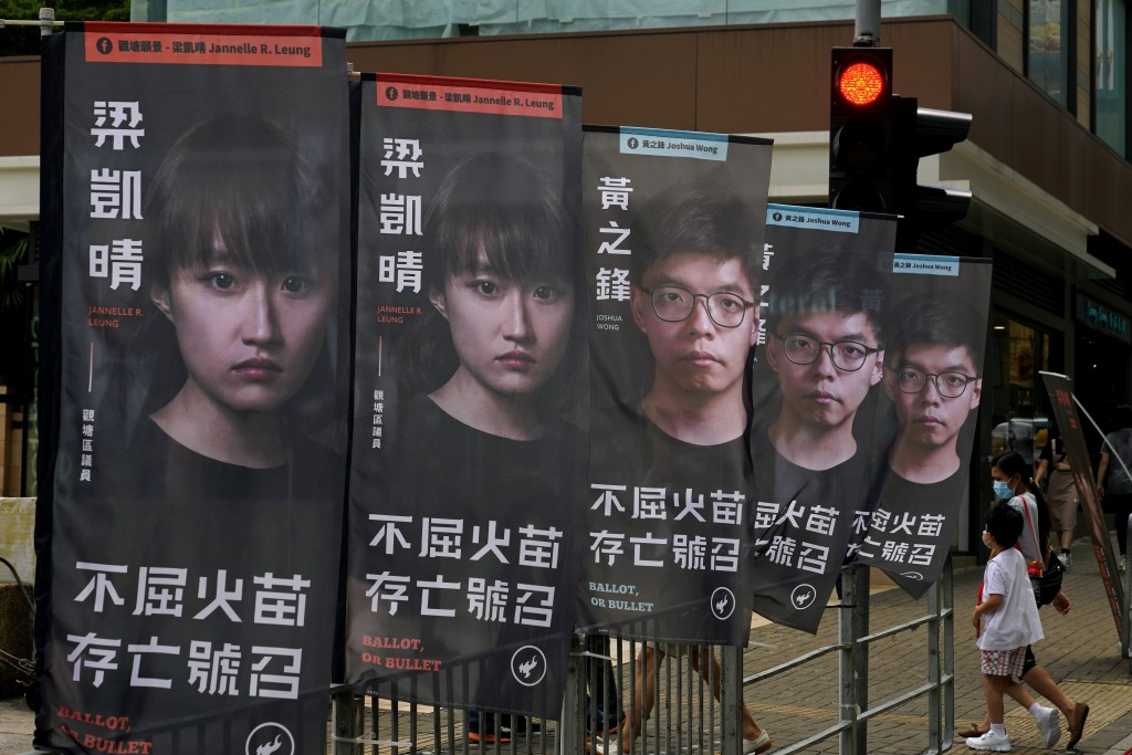 FILE - In this July 11, 2020, file photo, banners of a pro-democracy candidate Joshua Wong, wearing glasses, are displayed outside a subway station in...