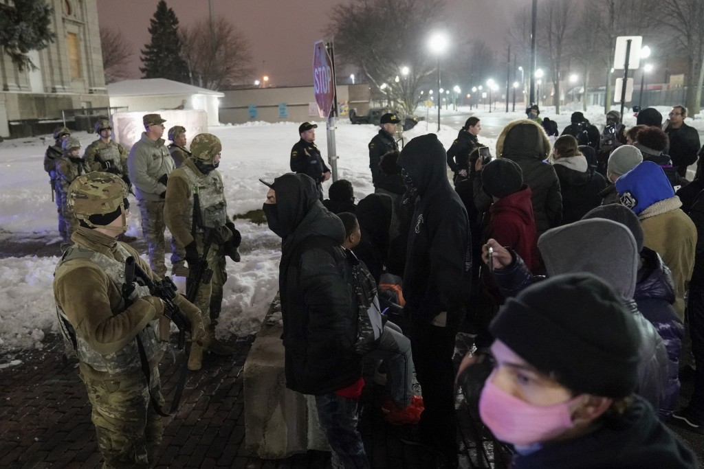 A group of protesters confront several National Guard members outside a museum, late Tuesday, Jan. 5, 2021, in Kenosha, Wis. Earlier it was announced ...