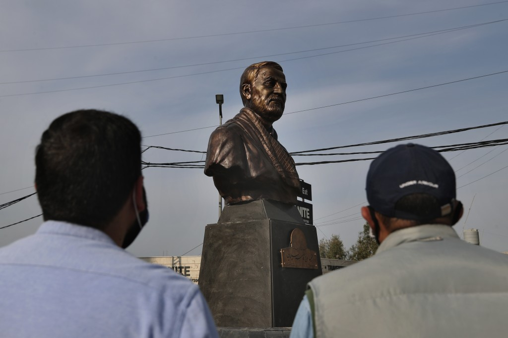 Hezbollah supporters look at a statue of Iranian General Qassem Soleimani, head of Iran's Quds force, installed to commemorate the anniversary of his ...