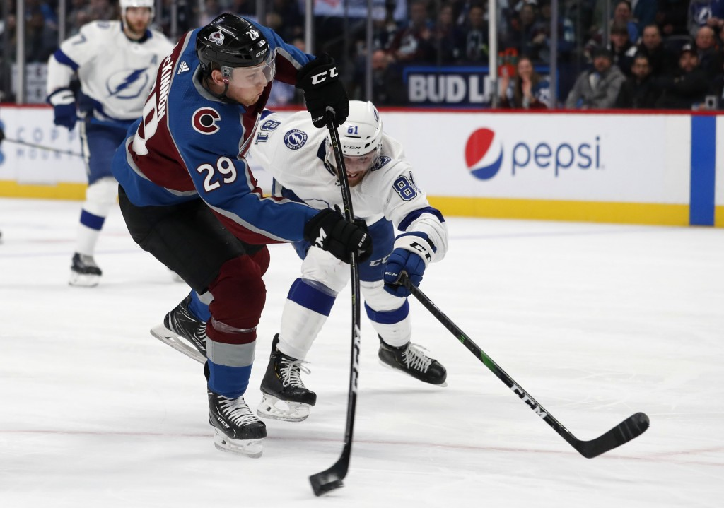 FILE - Colorado Avalanche center Nathan MacKinnon, front, fires the puck as Tampa Bay Lightning defenseman Erik Cernak covers in the first period of a...