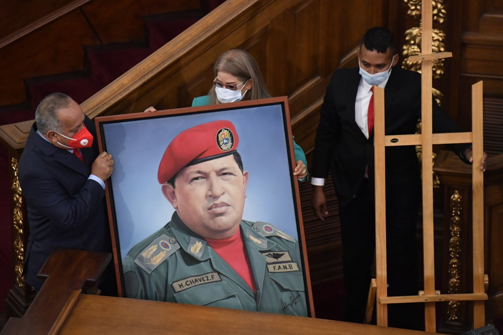 First Lady Cilia Flores, center, and Socialist party leader Diosdado Cabello, left, carry a portrait of late Venezuelan President Hugo Chavez into the...