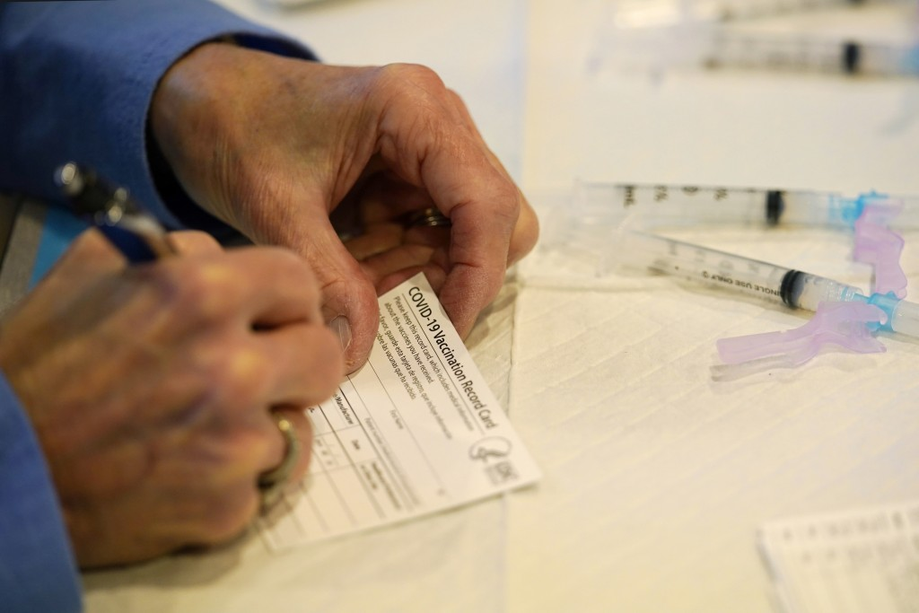FILE - In this Tuesday, Dec. 29, 2020 file photo, a county health department worker fills out a vaccination record card before administering the Moder...
