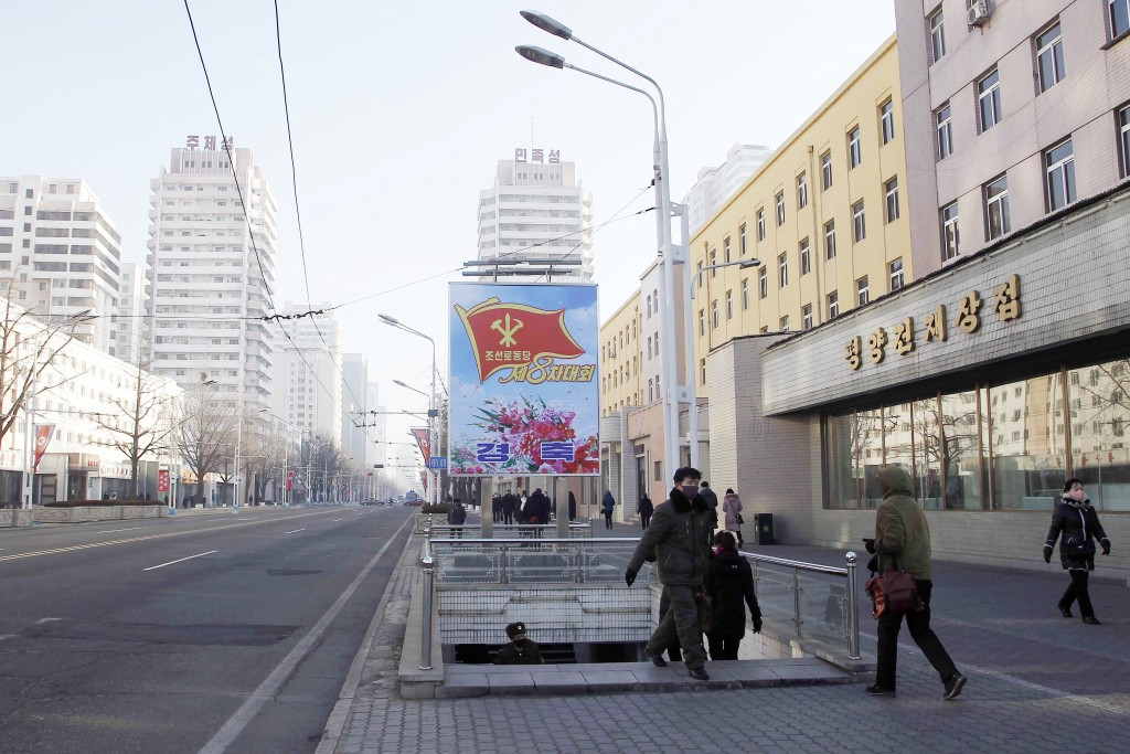 People walk past a billboard announcing the 8th Congress of the Workers Party along a main street of the Central District in Pyongyang, North Korea, o...