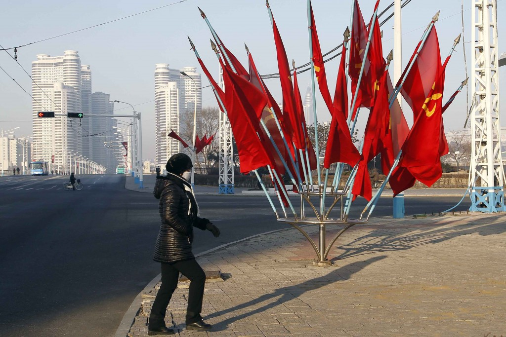 A person passes by a bouquet of Workers Party flags along a main street of the Central District in Pyongyang, North Korea, on Wednesday, Jan. 6, 2021....