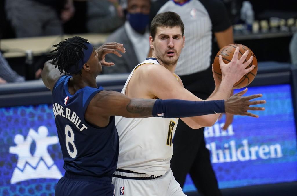 Denver Nuggets center Nikola Jokic, right, looks to pass the ball as Minnesota Timberwolves forward Jarred Vanderbilt defends during the first half of...