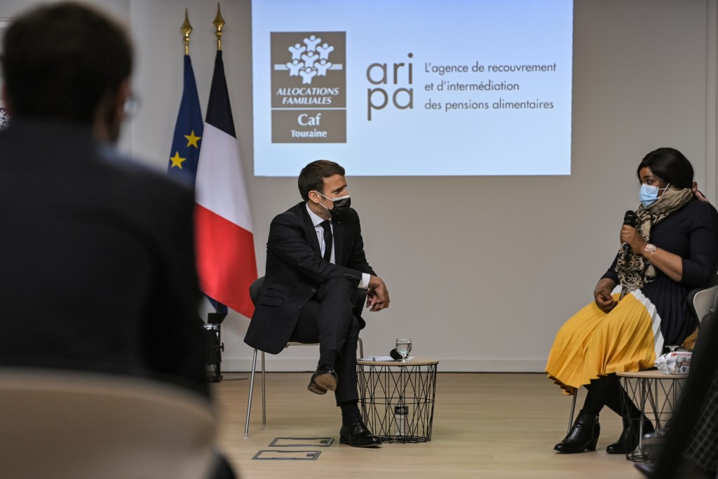 French President Emmanuel Macron, left, attends a meeting during a visit at the headquarters of the local CAF (French family allowance public services...