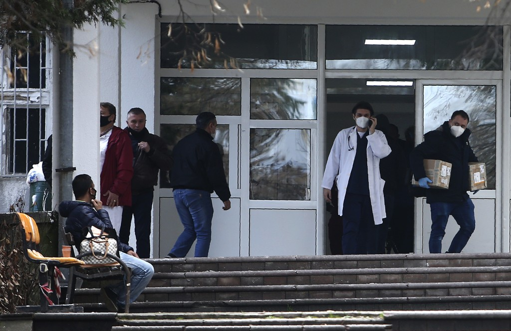 In this picture taken on Tuesday, Dec. 29, 2020, people and health workers are pictured in front of the entrance of the University Clinic complex in S...