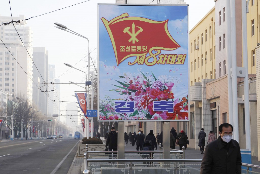 People walk past a billboard announcing the 8th Congress of the Workers' Party along a main street of the Central District in Pyongyang, North Korea, ...
