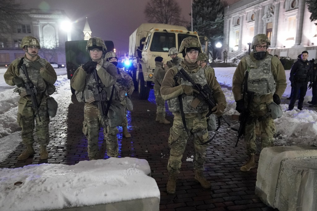 National Guard members stand outside a museum, late Tuesday, Jan. 5, 2021, in Kenosha, Wis. Earlier it was announced that no charges will be filed aga...