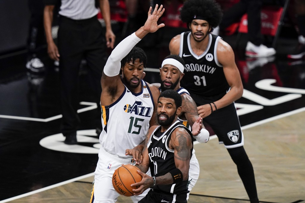 Utah Jazz's Derrick Favors (15) defens Brooklyn Nets' Kyrie Irving (11) during the second half of an NBA basketball game Tuesday, Jan. 5, 2021, in New...
