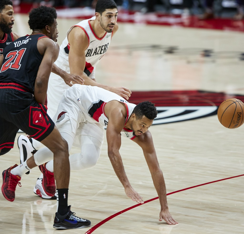 Portland Trail Blazers guard CJ McCollum, right, is tripped by Chicago Bulls forward Thaddeus Young during the first half of an NBA basketball game in...