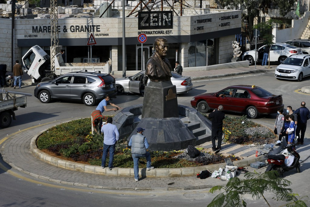 People gather near a statue of Iranian General Qassem Soleimani, who was the head of Iran's Quds force, that was installed to commemorate the annivers...
