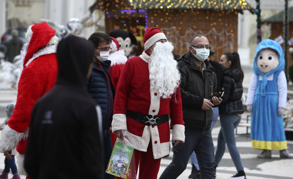 In this picture taken on Tuesday, Dec. 29, 2020, men dressed as Santa Claus hang around, as people wearing face masks walk through downtown Skopje, No...